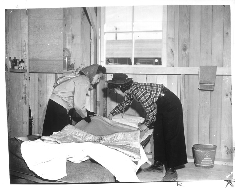 """""""In unpainted cabin whose wall supports remain to be covered, these Jap girls arrange one of the narrow cots.""""--caption on photograph"""