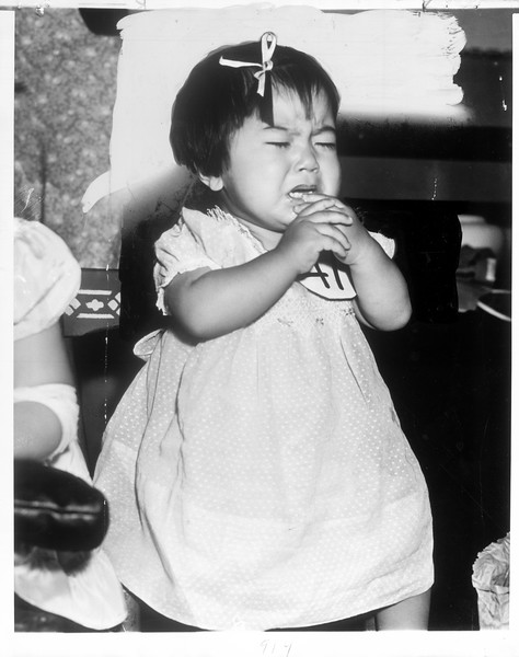 """""""Little Setsuka Foruta got a little tired during judging of 125 third generation Japanese tots yesterday.  She wrinkled up her eyes, put hands to her mouth and sobbed.""""--caption on photograph"""
