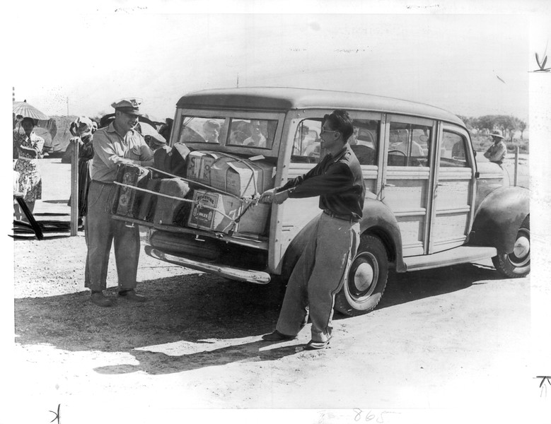 """Pack -- Baggage of Japanese who have just signed out of Manzanar is secured to a WRA station wagon before leaving for Reno"" -- caption on photograph"