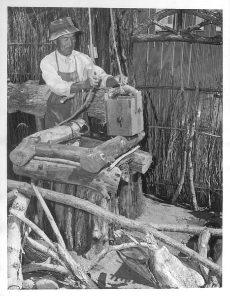 """George S. Takemura, landscape artist from West Los Angeles, builds a rustic wishing well at Manzanar, a War Relocation Authority center where evacuees of Japanese ancestry will spend the duration.""--caption on photograph"