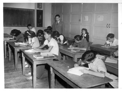 """A scene in one of the classrooms of the Daini Gakuen School here, where students learn to read and write the Japanese language and are taught Japanese customs"" -- caption on photograph"