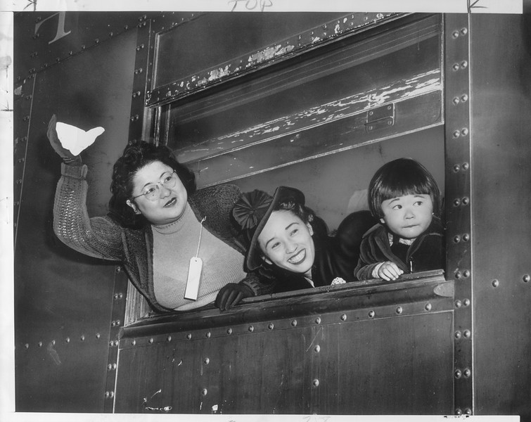 """""""No tearful farewells marked the exodus yesterday.  Smiling at prospect of new, exciting life, Japs waved good-by to a Los Angeles they won't see for duration.""""--caption on photograph"""