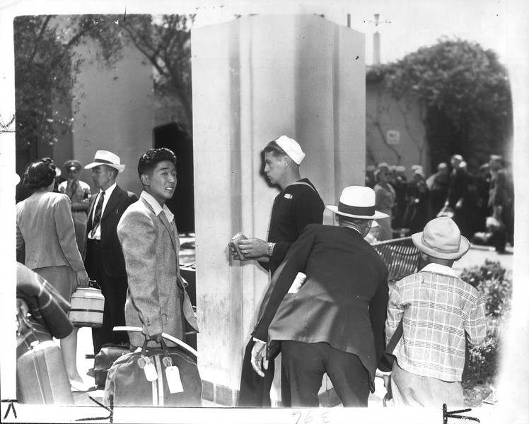 """""""Dramatic Meeting -- As 36 more Japanese returned to the Southland yesterday, they passed many service men on their way to battle zones.  Here a sailor stares at a young evacuee.""""--caption on photograph"""