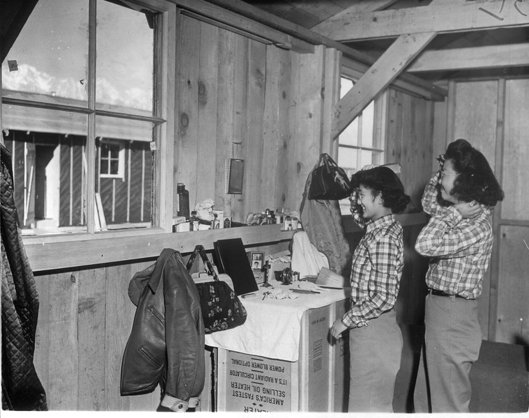 """""""Through window at left, these Jap girls at Manzanar may see the snowy grandeur of the mountains.  Japaanese decorating ingenuity will have walls covered soon.""""--caption on photograph"""