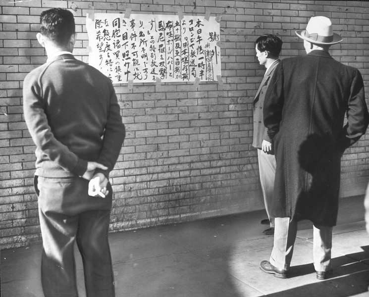 """Japanese in Little Tokyo are shown watching bulletins as the war started"" -- caption on photograph"
