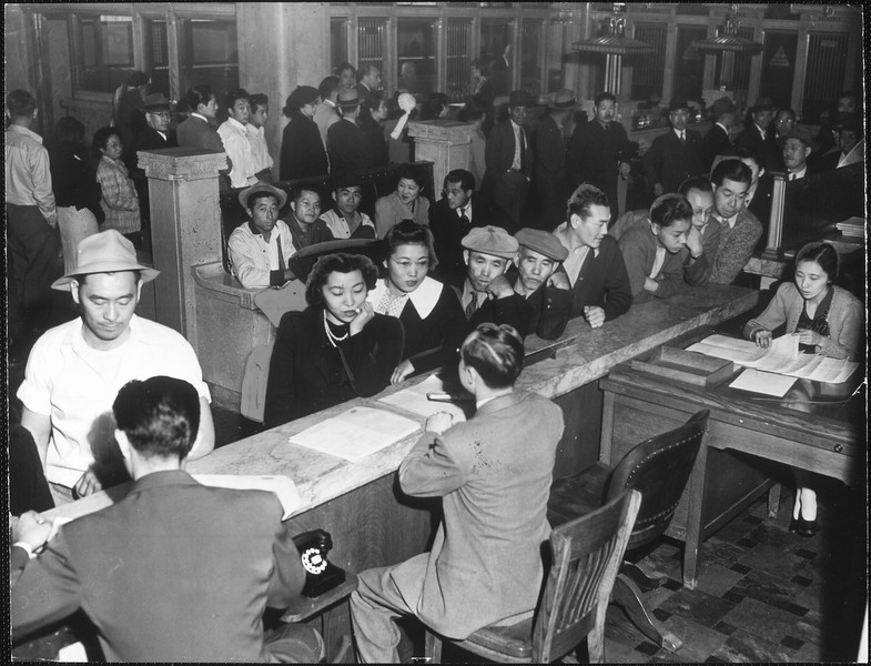 """Part of the 2000 Japanese who registered yesterday for the trip to Manzanar colony are shown above in offices of the Wartime Civilian Control Administration on Spring street"" -- caption on photograph"