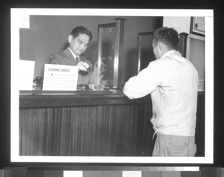 """George Haramoto (Nisei), teller at the branch of the California Bank in Los Angeles, located in the Japanese quarter of the city, shown taking care of a customer.""--caption on photograph"