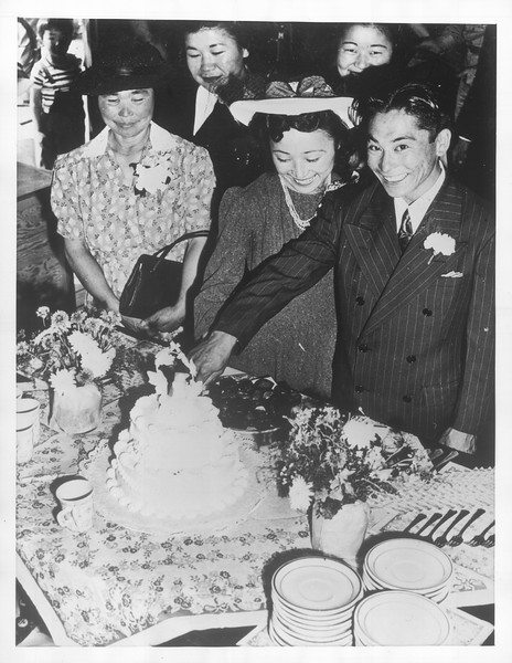 """""""Happy couple, Toya and Pete Matayoshi, 'Just Married' are shown cutting the wedding cake at Santa Anita Assembly Center.""""--caption on photograph"""