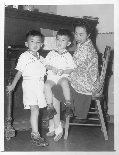 """Tetsuya Tanabe (left) and his brother, Roy Tanabe, both Sensei, singing in a Japanese kindergarten as their teacher, Mrs. F. Kitagawa (Nisei), plays the piano.""--caption on photograph"