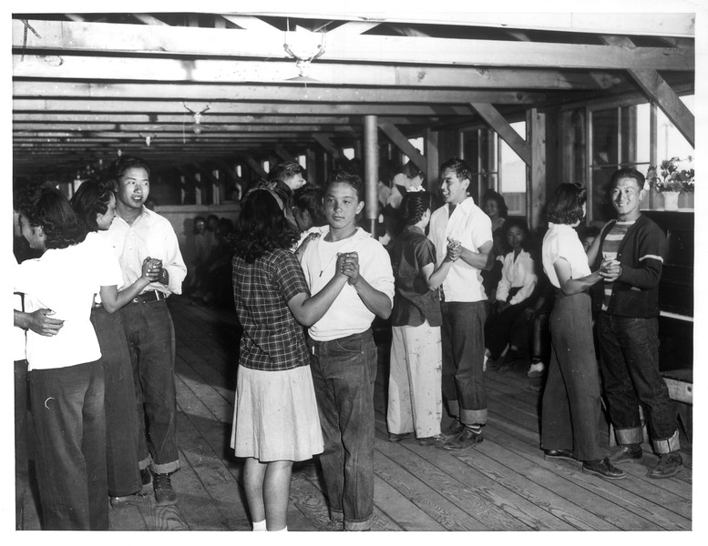 """Dancing is among the most popular diversions for the younger Japanese evacuees sent to Manzanar relocation center, as evidenced by this glimpse of several couples in a dancing class which is conducted in a girls' recreation hall.""--caption on photograph"