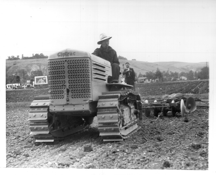 """""""G. Nagano (Nisei) cultivating truck garden with tractor at Gardena.  The most modern equipment is used on this farm.""""--caption on photograph"""