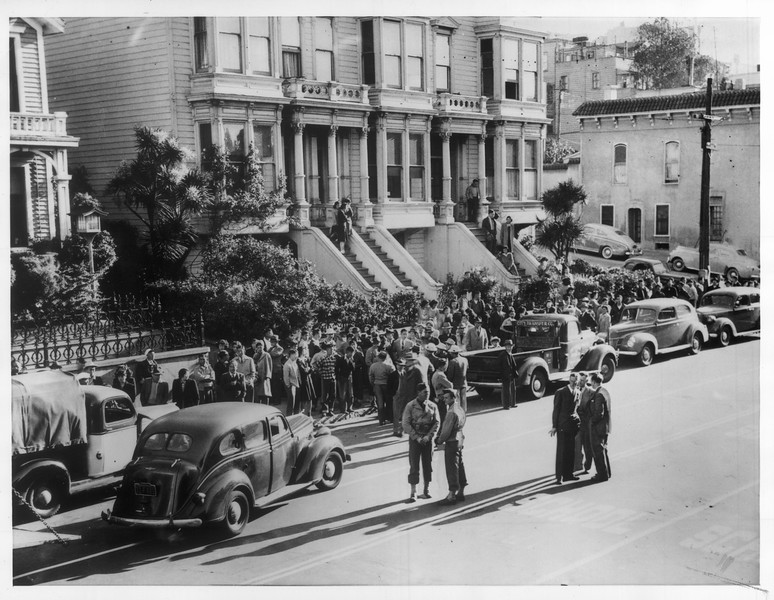 """""""A number of SF Japs crowd Bush St. sidewalk in preparation for their transfer to evacuation center for them at Tanforan -- Soldier escorts shown forground.""""--caption on photograph"""