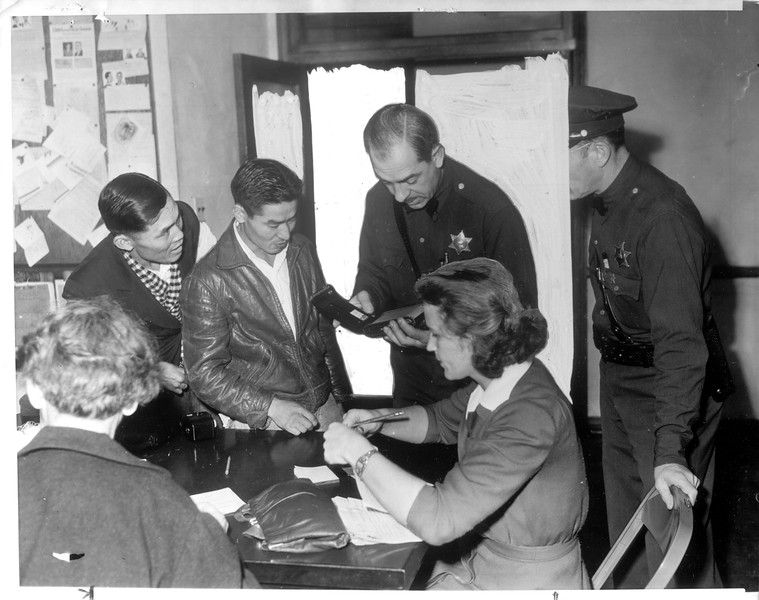 """""""Two Japanese nationals, Shinicki Hamamato and Sachio Kitani turn in their cameras to Deputy Sheriff A. F. Brehm.  Seated at right is a civilian defense worker, Mrs. W. G. Neilsen.""""--caption on photograph"""