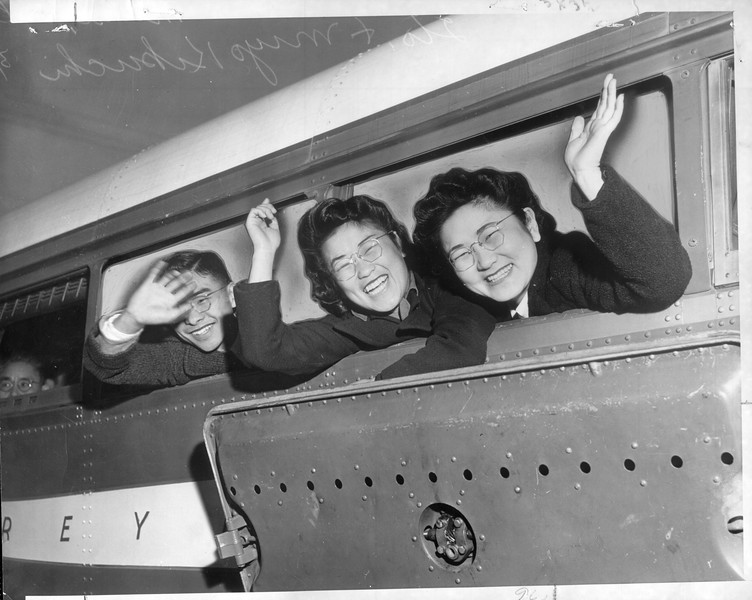 """""""Philosophic acceptance of Uncle Sam's edict, that they be evacuated from coastal areas is manifested by this trio of Japanese on the specially chartered bus [...] which took off for the Owens Valley concentration camp yesterday"""" -- caption on photograph"""