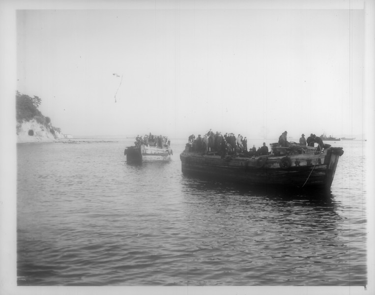"""""""Repatriates Reach Japan -- Cast off by the tugboat which brought them near shore, two Japanese barges, carrying repatriates from the liner Matsonia, come into the dock at Uraga on Christmas Day"""" -- caption on photograph"""