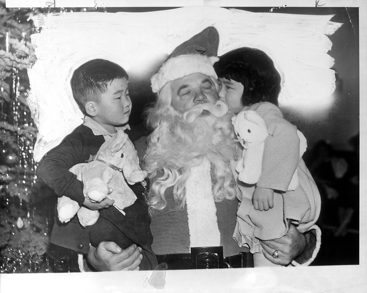"""Japanese orphans, good Americans, were not forgotten by Santa.  At a Fraternal Order of Eagles (Hollywood) party, Joe Mari and Sumi Kukasowa met St. Nick.""--caption on photograph"