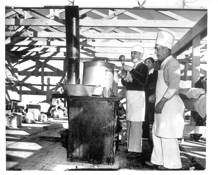 """Yet to be covered, rafters are the only roof over the heads of these Jap cooks who are pictured preparing meals for some of the first arrivals at the Manzanar camp.""--caption on photograph"
