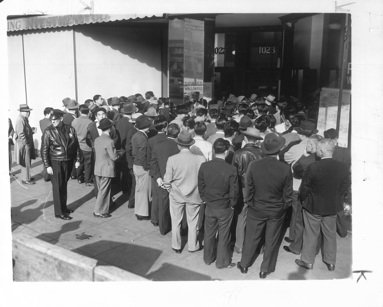 """In preparation for their removal to reception centers and employment projects in the interior.  Japanese aliens and Japanese-American citizens are pictured registering at downtown office.""--caption on photograph"