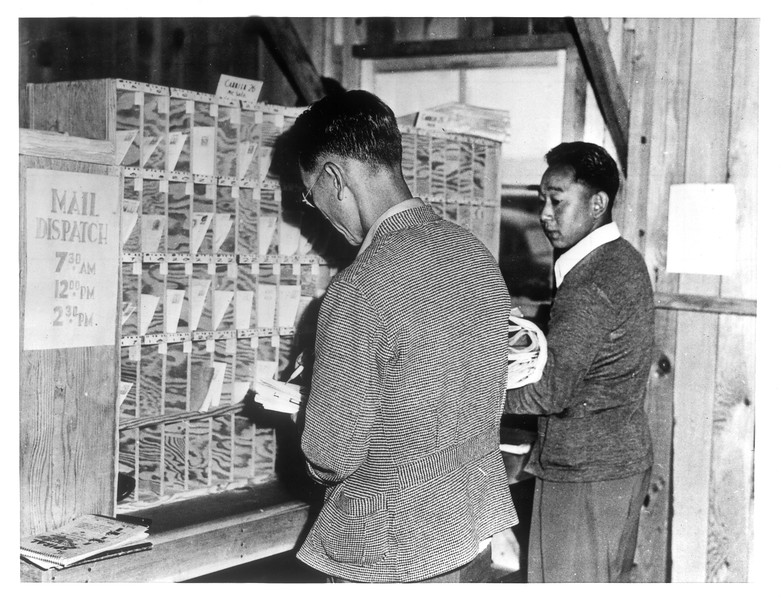 """Mail Dispatchers -- Mail clerks segregate the mail in the Santa Anita Assembly Center Postoffice for the postman.""--caption on photograph"