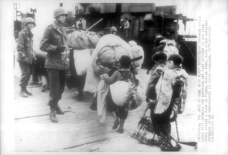 """""""Japs Go Home with Heavy Burdens -- A Japanese child laden with bundles and carrying her tiny brother on her back trods across a pier in Fusan, Korean port, with other burdened Japanese being repatriated to their homeland.""""--caption on photograph"""