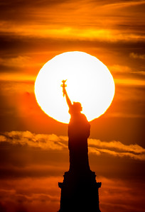 Setting Sun behind the Statue of Liberty