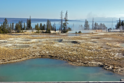Additional geyser pools in Yellowstone, Yellowstone Lake in background.