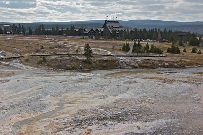 Additional geyser pools in Yellowstone, Old Faithful Inn in background.