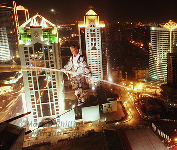 Jay Cochrane tests the wire during practice for the Shanghai Tourism Festival in the PuDong region of Shanghai the day before the actual skywalk. He accomplished a world record for the highest and longest nighttime building-to-building wire walk on September 24, 1996.