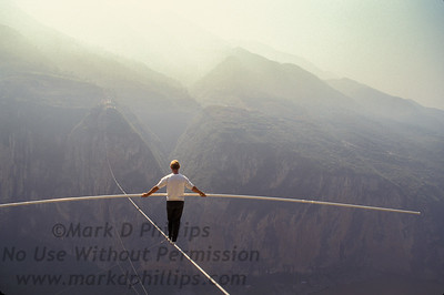 """Jay Cochrane, """"The Prince of the Air"""", practices for his skywalk over the Yangtze River in Qutang Gorge, China, in 1995. The skywalk was and is the greatest ever made spanning half a mile between the canyon walls and 1,350 feet above the river."""