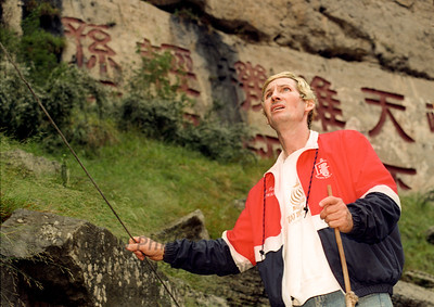 """Jay Cochrane checks a guide wire for the Great China Skywalk over the Yangtze River deep in Qutang Gorge on October 19, 1995. The letters on wall behind are ancient, naming the gorge, and were covered by water after the completion of the Three Gorges Dam. The Chalk Wall, several hundred meters wide and several dozen meters high, is a canvas completely covered with carved inscriptions dating from as far back as the Song Dynasty, 1,000 years ago. Two characters named """"Qutang Gorge"""" were carved by Zhang Boxiang of the Qing Dynasty over 400 years ago, each measuring 1.70 meters in width."""