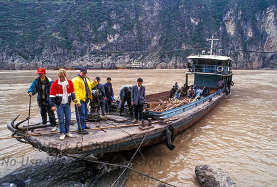 """Jay Cochrane, """"The Prince of the Air"""", rides across the Yangtze River on a flat boat in Qutang Gorge."""