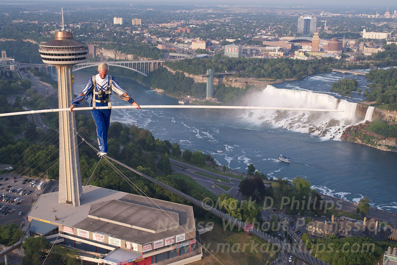 Jay Cochrane skywalks above the American Falls and Fallsview Avenue in Niagara Falls during the first performance of Skywalk 2012, the Greatest Building to Building skywalk in North American history. Cochrane will grace the Niagara skyline from the Skylon Tower (520 feet tall) to the top of the Hilton Hotel (581 feet tall) for the entire summer. At 1300 feet distance, he will cover approximately 30 Kilometers (20 miles) on this wire in the 81 scheduled performances.  Photo by ©Mark D Phillips