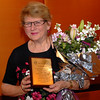 Jean Haste is surprised to receive a plaque and a nice bunch of flowers!