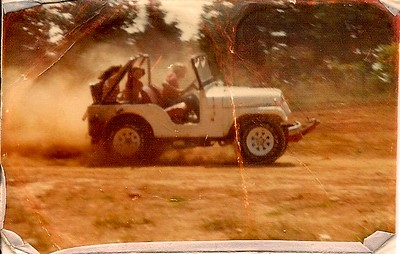 Here's the same 1966 Jeep Tuxedo Park  in action. I think this was taken sometime in 1978??? As you can see, my Uncle added wagon wheels and bigger tires. Also, check out the tow bar on the front. I brought it to VB for a summer, and broke the transmission while leaving a stoplight, so home it went. I think my younger brother took this. It's me driving, with my cousins, Heather & Nancy in the back. This is a scan from a wallet-sized photo. I have an 8x10 enlargement somewhere in this house, and when I find it, I will scan it and post it.