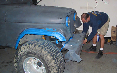 Sandman wrapping the bumper prior to painting