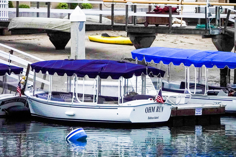 """A Balboa Island """"Duffy"""" boat is docked in Newport Harbor at early morning."""