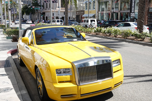 A big yellow Rolls Royce is parked on Rodeo Drive--and has a parking ticket for parking too long.