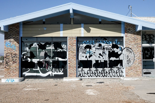 If you look closely, you can see that vandals are trying to say something with the broken windows and grafitti in Baker, California