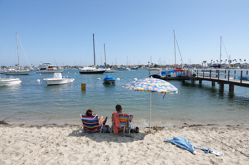 Relaxing on the small beach on lower Newport Harbor