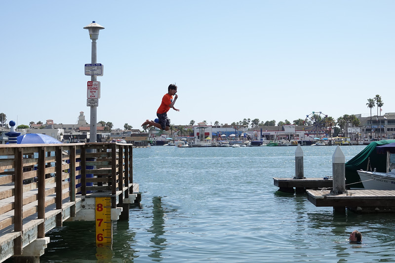 Jumping off a dock into the waters of lower Newport Harbor, which separates Balboa Island and Balboa Peninsula.