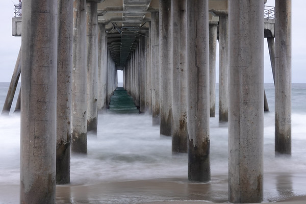 Underneath the Huntington Beach Pier at dusk, using a slow shutter to make the waves look dreamy like.