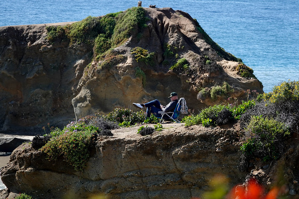 A man relaxes and catches up on his smartphone from a folding chair in Heisler Park