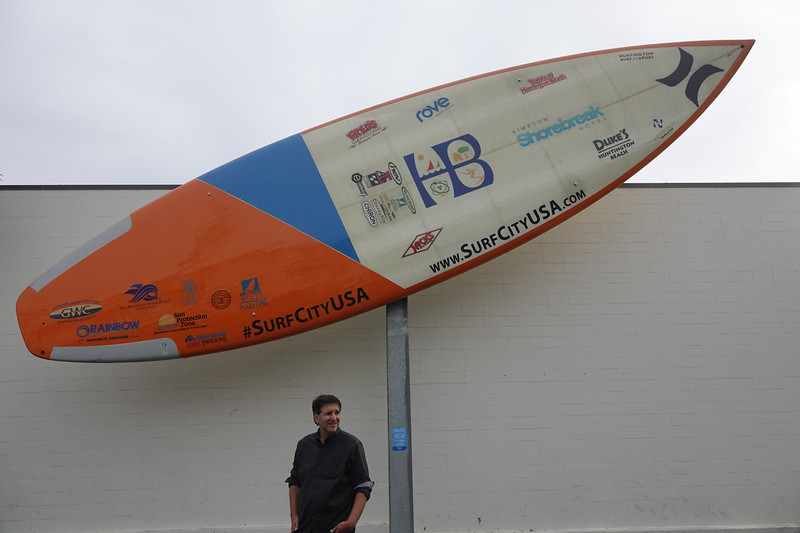 Jefferson Graham in front of the world's largest surfboard, which is on display at the International Surfing Museum in Huntington Beach