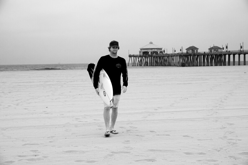 The classic holding the surfboard shot with the Huntington Beach Pier in the background