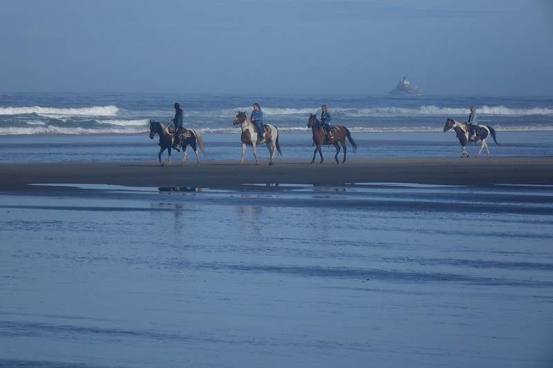 Riding horseback in early morning on Cannon Beach, with the lighthouse behind.