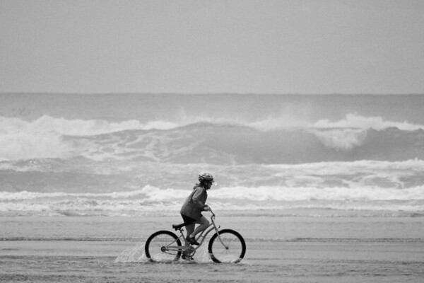 Cyclists get to ride along the sand--and in the water, on the shores of Cannon Beach, Oregon