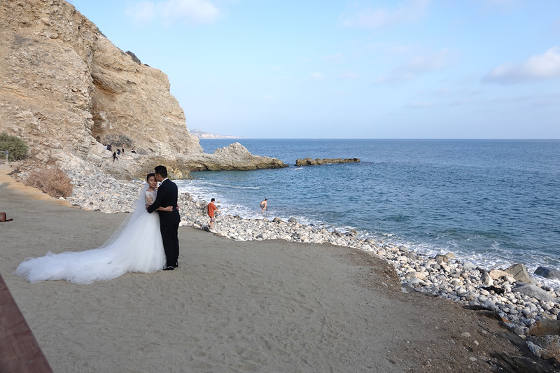 A couple poses on the beach before getting married