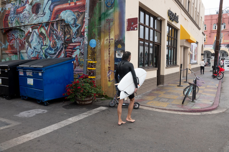 A barefoot surfer walks by a mural on Pacific Aven ue in Venice