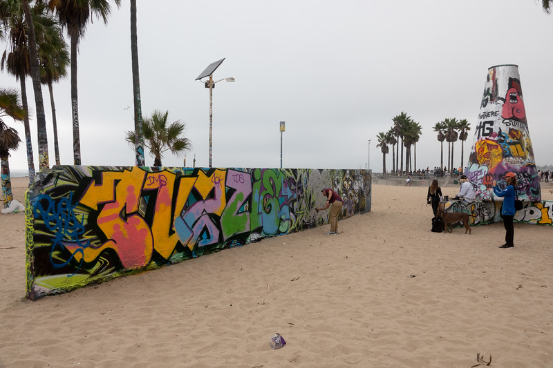 Using spray paint to paint a public mural space in Venice Beach.