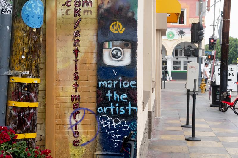 Local artist Marioe signs her mural work in Venice